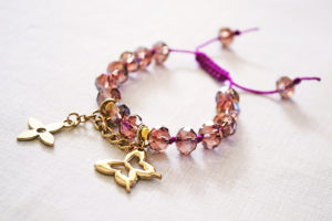 still life of bracelet with purple beads and gold charms