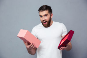 Portrait of a young man opening gift box over gray background